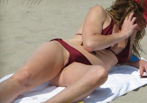 Image 1: Oops Son gros clitoris depasse du string a la plage