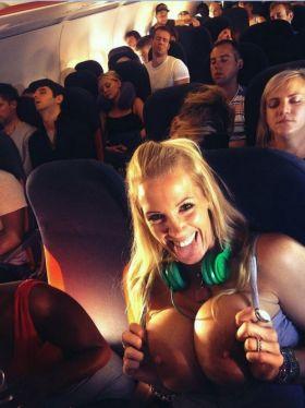 Cette jeune femme blonde un peu folle exhibe ses gros seins dans un avion