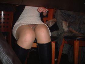 Un voyeur prend une photo d'une coquine sans culotte sous la table