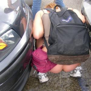 Fille qui fait pipi entre 2 voiture...