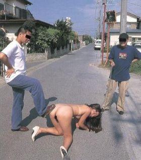 Deux hommes humilient une chienne soumise nue dans la rue